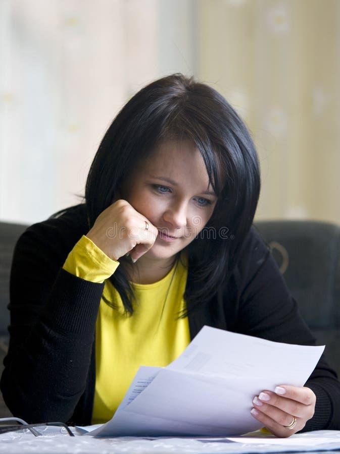 Positivo da mulher sobre suas contas imagem de stock royalty free