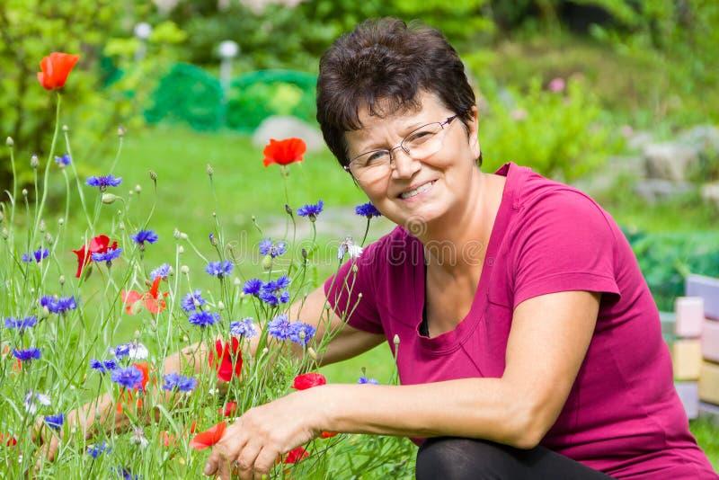 Positivt högt kvinnasammanträde bland blommor i en trädgård arkivfoto