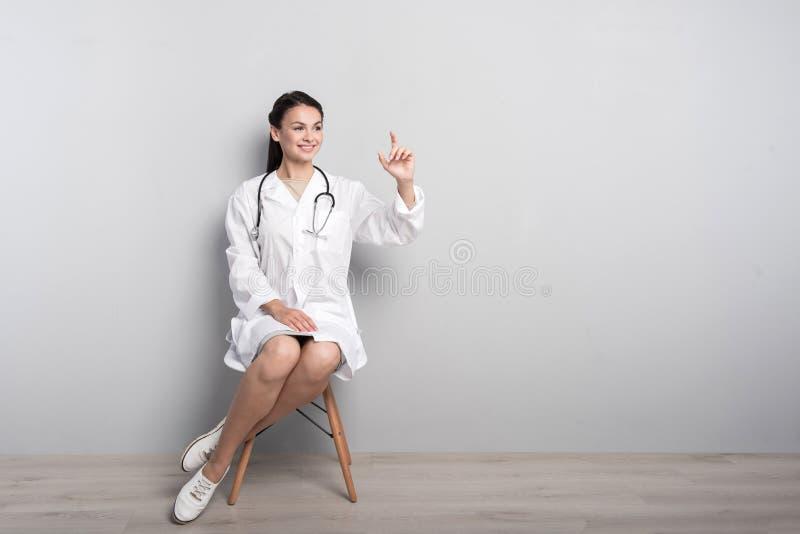 Positivt kvinnligt doktorssammanträde i stolen arkivbild