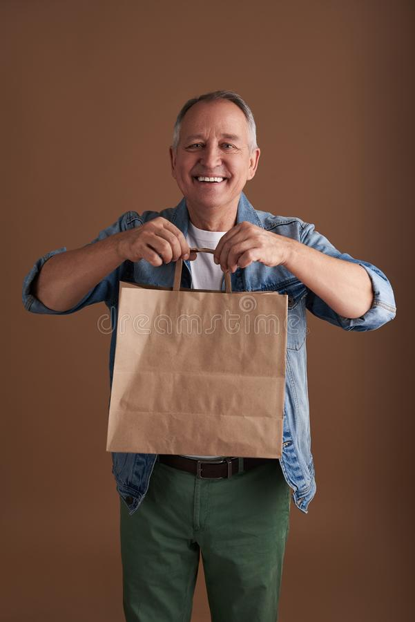 Positivt mananseende med papperspåsen och rymma dess handtag arkivbild