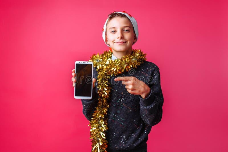 Positivt tonårigt i den Santa Claus hatten med glitter på hans hals, showin arkivfoto