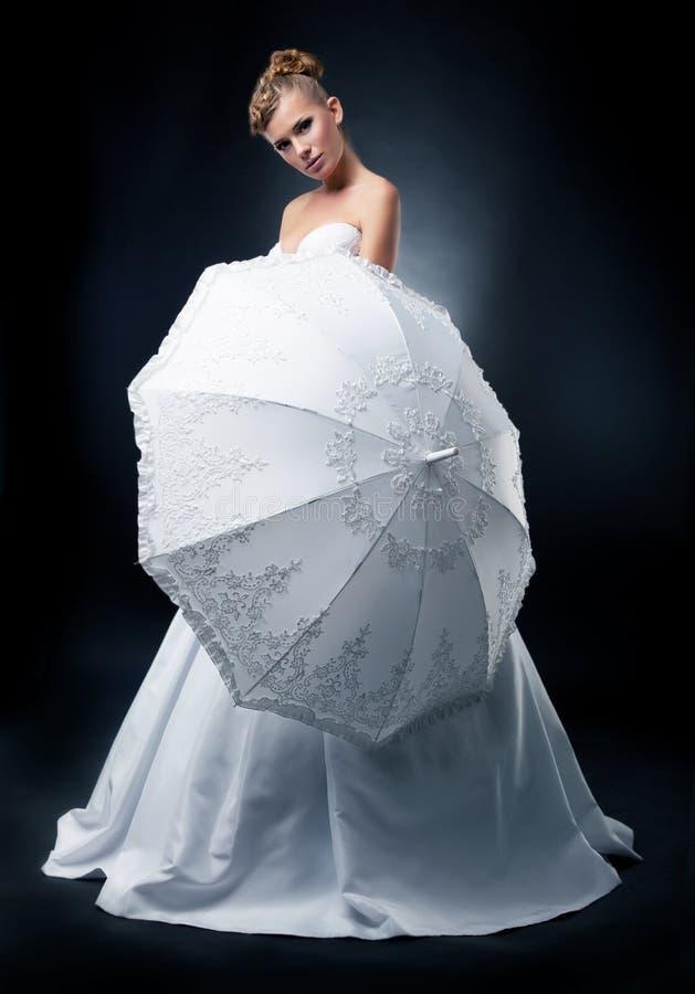 Posizione bionda della sposa sopra la priorità bassa nera immagine stock