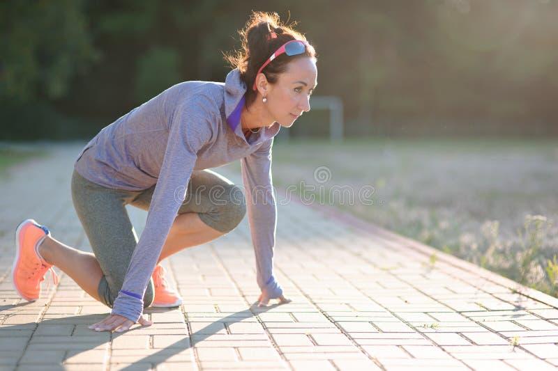 Posizione di inizio della ragazza dello sprinter sulla pista Sport pareggiante immagini stock