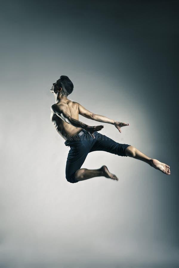 Posizione relativa alla ginnastica di salto dell'uomo caucasico su grey fotografia stock libera da diritti
