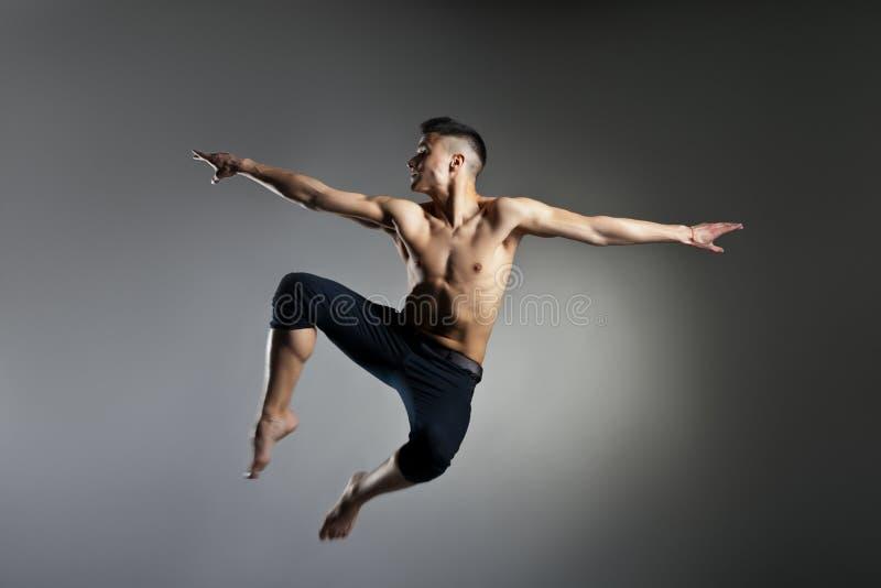 Posizione relativa alla ginnastica di salto dell'uomo caucasico su grey immagini stock libere da diritti