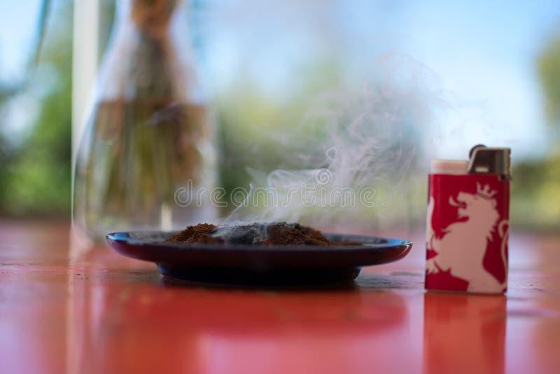 Poso que fuma al lado del encendedor rojo del le?n foto de archivo libre de regalías
