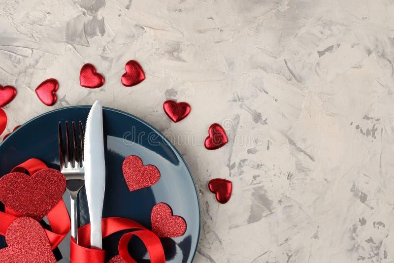 Posponga la regolazione Piatto blu con un coltello e una forcella e cuori rossi su un fondo del cemento leggero Giorno del `s del immagine stock