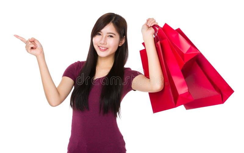 A posse asiática da mulher com saco de compras e o dedo apontam para cima fotos de stock