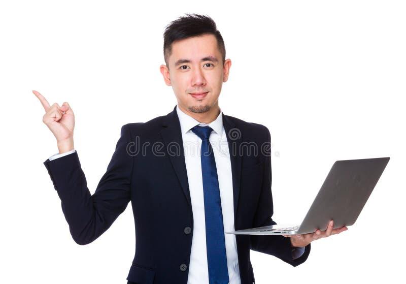 A posse asiática do homem de negócios com laptop e o dedo apontam u fotos de stock