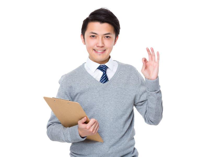 A posse asiática do homem de negócios com prancheta e o sinal aprovado gesticulam imagem de stock royalty free