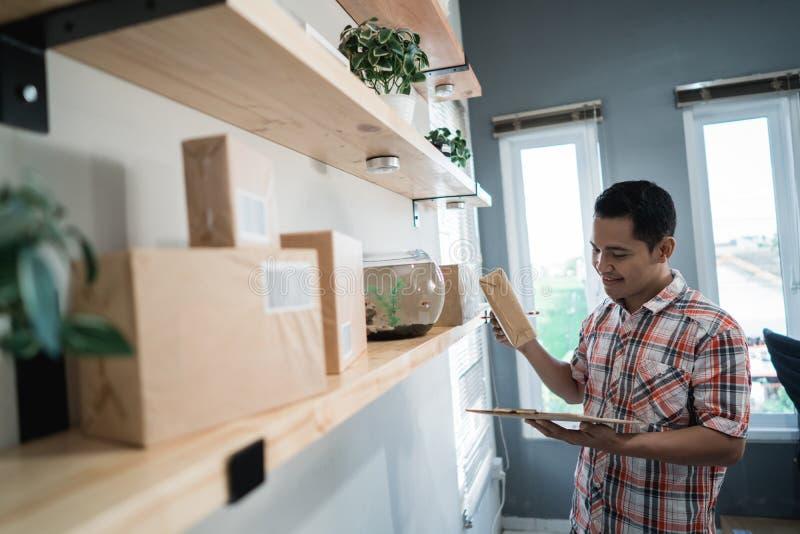 Posse asiática do trabalhador do homem e para verificar uma caixa para corrigir o endereço de destino fotografia de stock royalty free