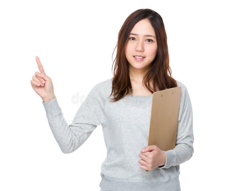 A posse da jovem mulher com prancheta e o dedo apontam acima foto de stock