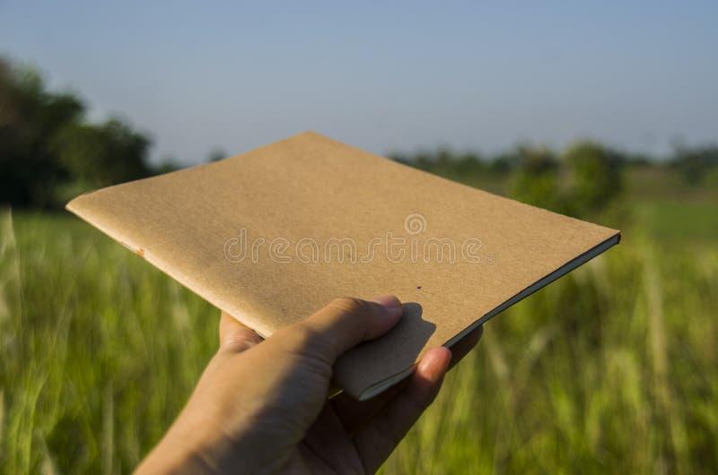 Posse da mão no caderno marrom com luz natural no jardim exterior em Chiang Ma, Tailândia fotografia de stock