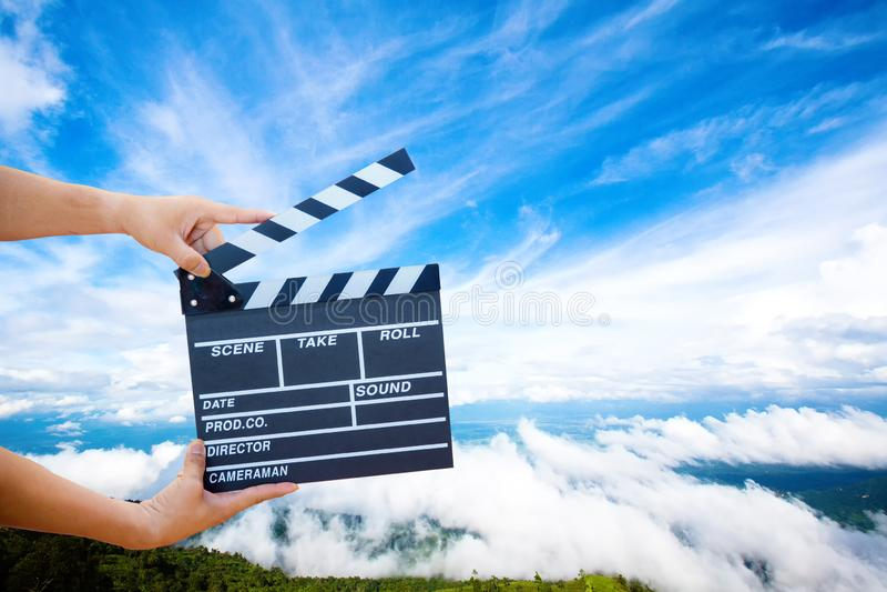 Posse da mão uma ardósia do filme com montanha e céu fotografia de stock royalty free