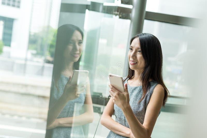 Posse da mulher de negócios com telefone celular e vista longe com vento imagem de stock