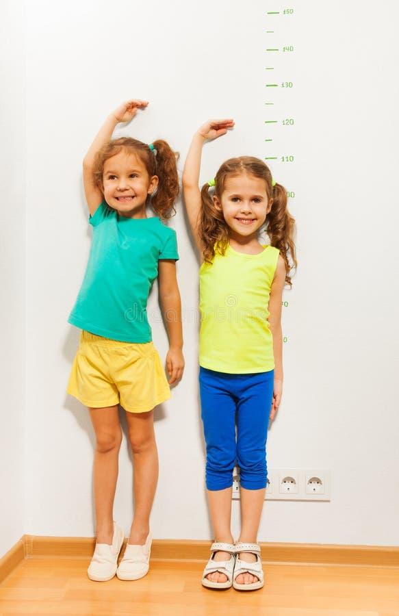 A posse de duas meninas cede a escala próxima da mão na parede foto de stock