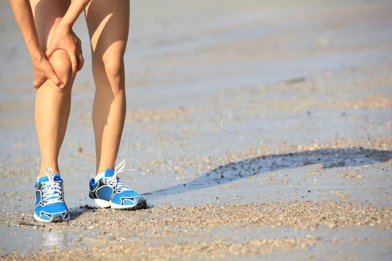 A posse do basculador da mulher da aptidão seus esportes feriu o pé no beira-mar foto de stock