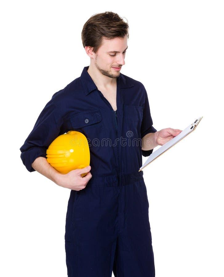 Posse do coordenador de construção com capacete de segurança e lida o relatório em c fotos de stock