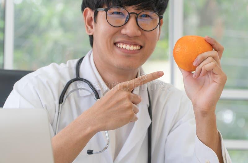 Posse do doutor ou do nutricionista alaranjada e para apontar seu dedo na laranja em e sorriso na clínica Dieta saud?vel Conceito fotos de stock royalty free