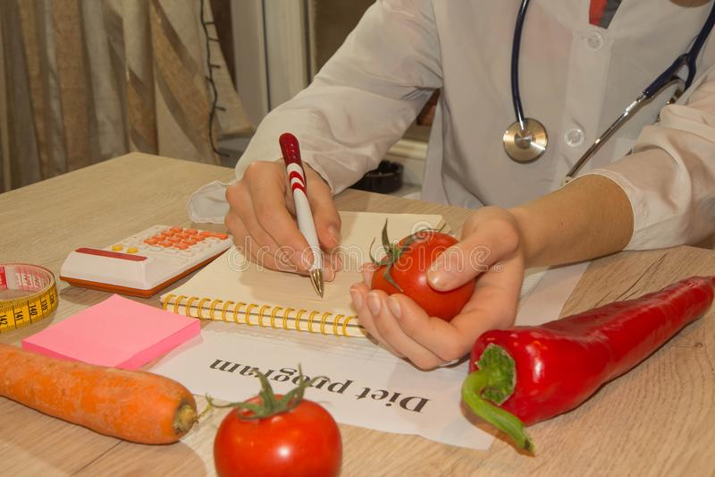 Posse do doutor ou do nutricionista um tomate Bom conceito médico da nutrição dos cuidados médicos foto de stock royalty free