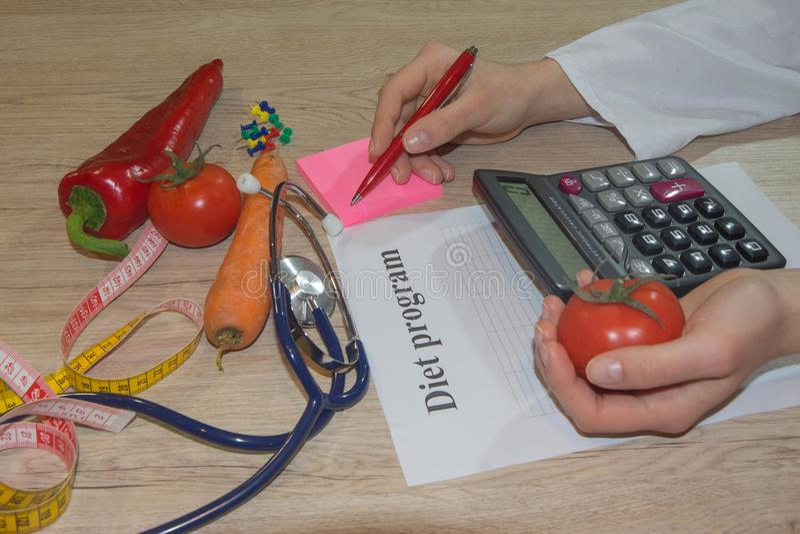 Posse do doutor ou do nutricionista um tomate Bom conceito médico da nutrição dos cuidados médicos fotos de stock royalty free
