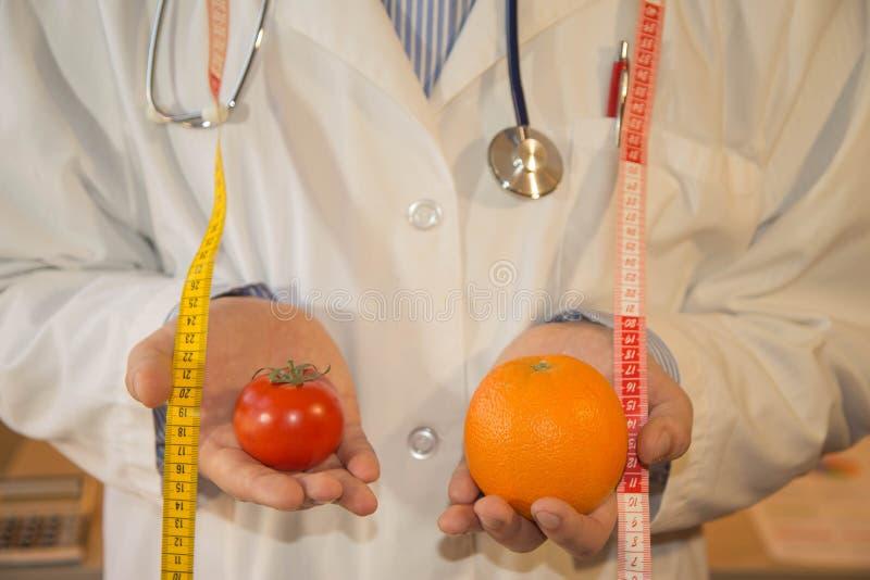 Posse do doutor ou do nutricionista um tomate e uma laranja Bom conceito médico da nutrição dos cuidados médicos Tomate e laranja foto de stock