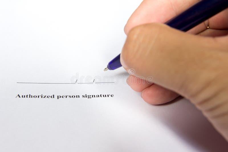 A posse do homem de negócio a pena para assina dentro a assinatura da autorização imagem de stock
