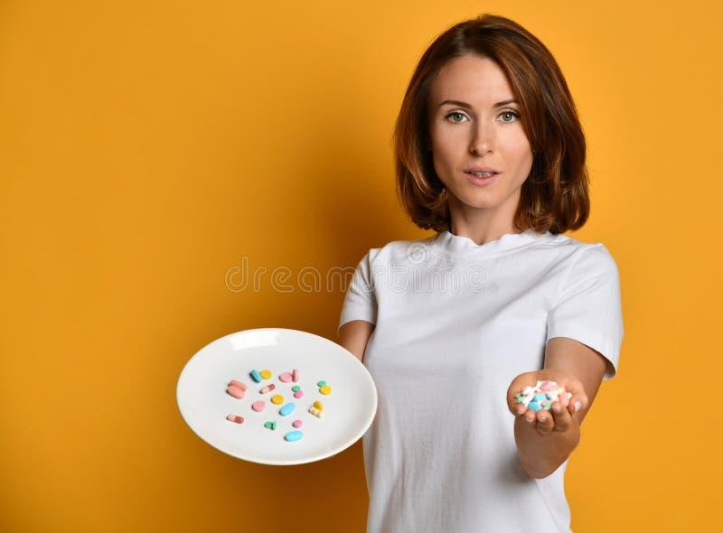Posse do nutricionista da mulher uma placa branca com as drogas diferentes da perda de peso da prescri??o dos suplementos diet?ti imagens de stock royalty free