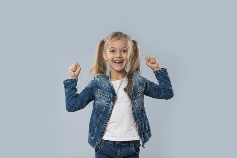 A posse entusiasmado da menina bonita entrega acima do revestimento de sorriso feliz das calças de brim do desgaste isolado fotografia de stock royalty free