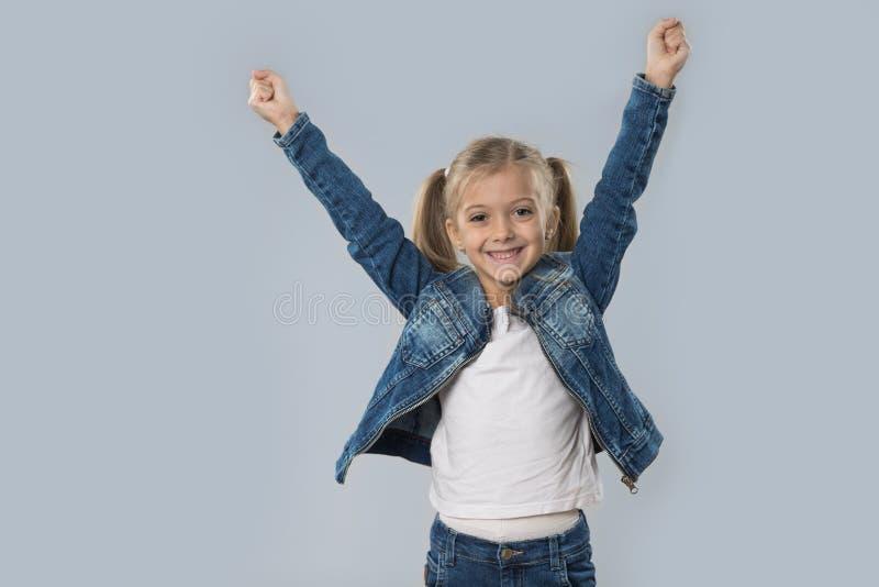 A posse entusiasmado da menina bonita entrega acima do revestimento de sorriso feliz das calças de brim do desgaste isolado fotos de stock royalty free