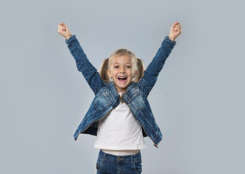 A posse entusiasmado da menina bonita entrega acima do revestimento de sorriso feliz das calças de brim do desgaste isolado imagens de stock royalty free
