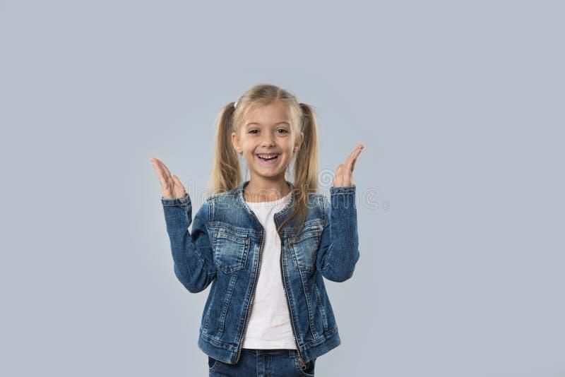 A posse entusiasmado da menina bonita entrega acima do revestimento de sorriso feliz das calças de brim do desgaste isolado foto de stock royalty free