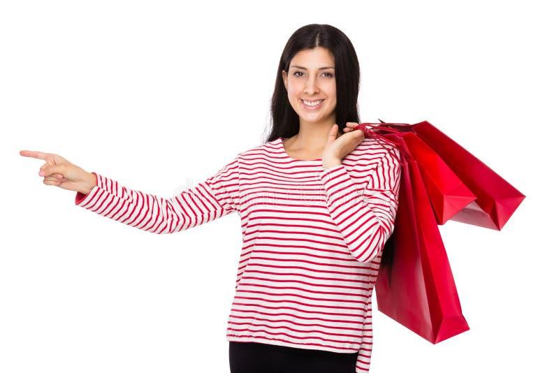 A posse indiana misturada da mulher com saco de compras e o dedo apontam de lado imagens de stock