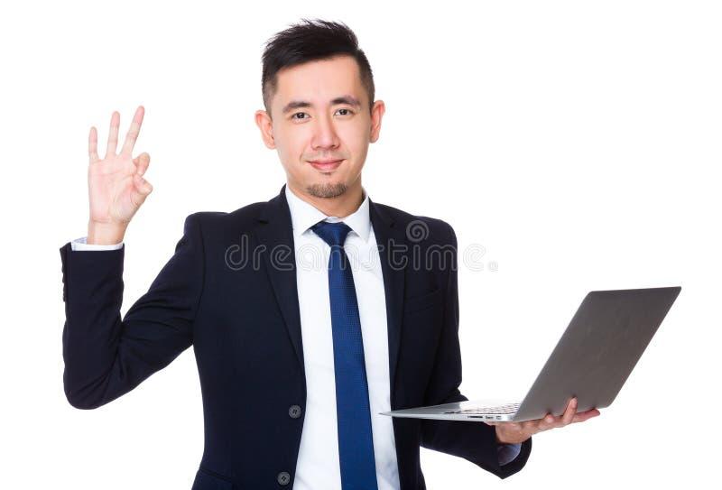 A posse nova do homem de negócios com laptop e o sinal aprovado gesticulam foto de stock