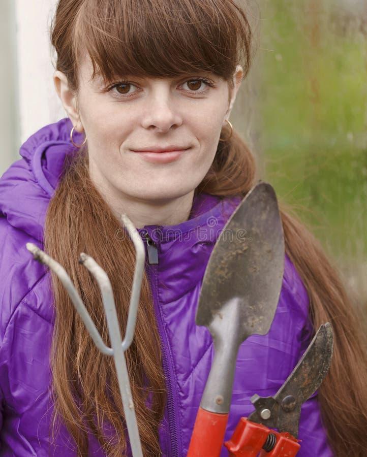 Posses de olhos castanhos da menina na frente dele ferramentas de jardinagem Retrato do close-up de imagem de stock royalty free