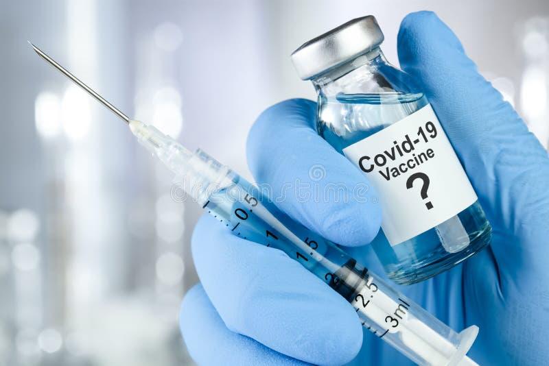 Possibile cura con una mano in guanti medici blu che tengono in mano Coronavirus, virus Covid 19, fiale vaccino fotografia stock