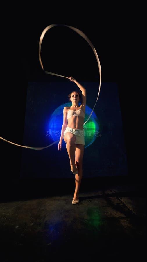 Possibilidade remota de um treinamento novo bonito da mulher da ginasta com fita da ginástica imagens de stock