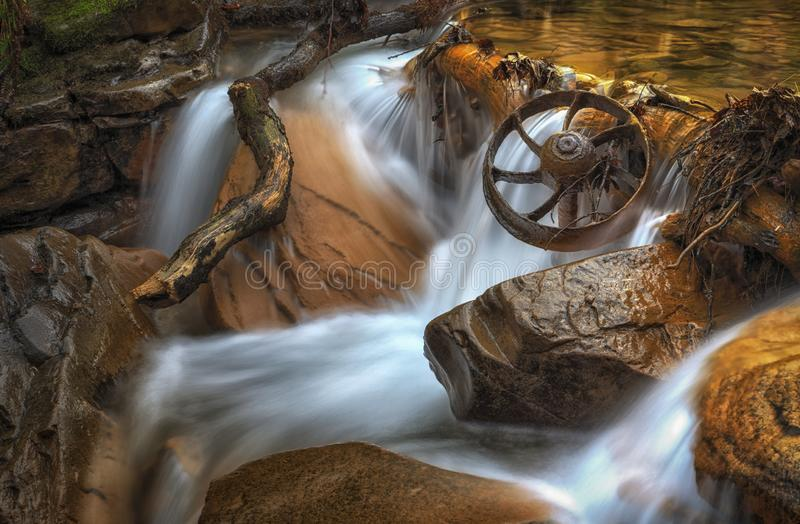 Coal Mining Wagon Wheel. Possibly a wheel from an abandoned Welsh coalmine, in the river at Melincourt Brook, Resolven, South Wales, UK royalty free stock photography