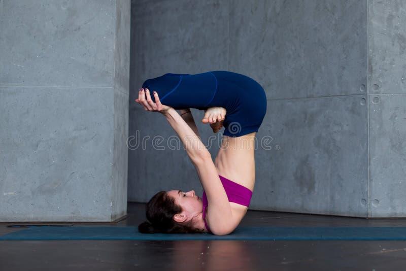 Postępowy młody yogini ćwiczy Hatha joga stoi w przestawnej lotos pozie, padmasana, na macie obraz royalty free