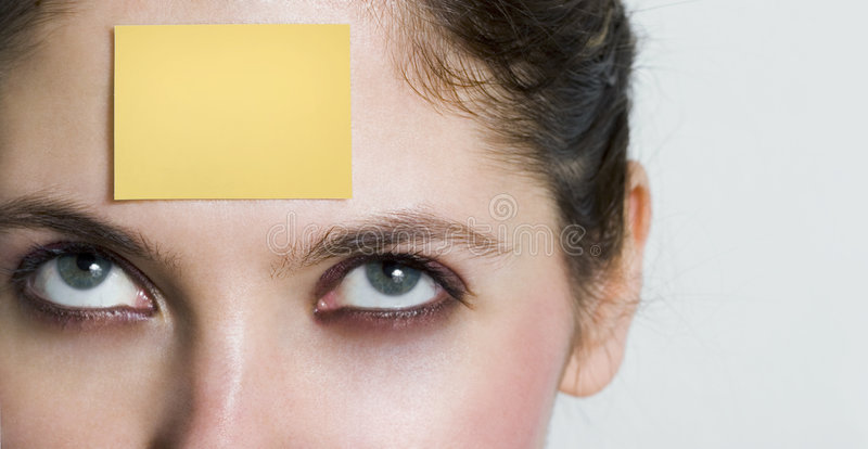 Post-it. Girl looking up to a yellow post it sticked on her forehead. You can write whatever you want over it stock photography