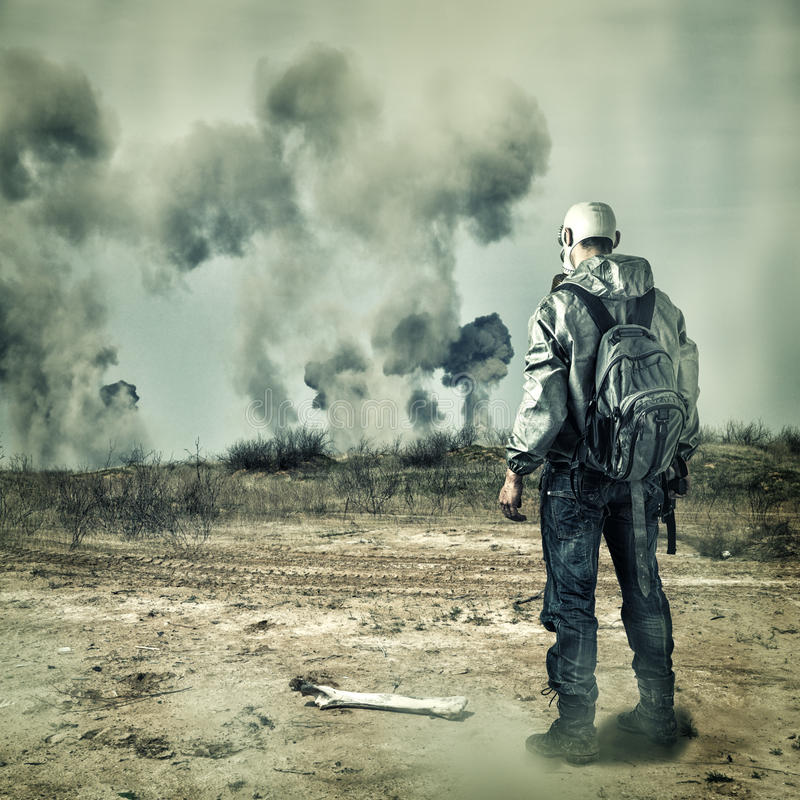 Post apocalypse. Man in gas mask, explosions. Post apocalypse. Man in gas mask with handgun and back pack in apocalyptic world looking on explosions on horizon stock photography
