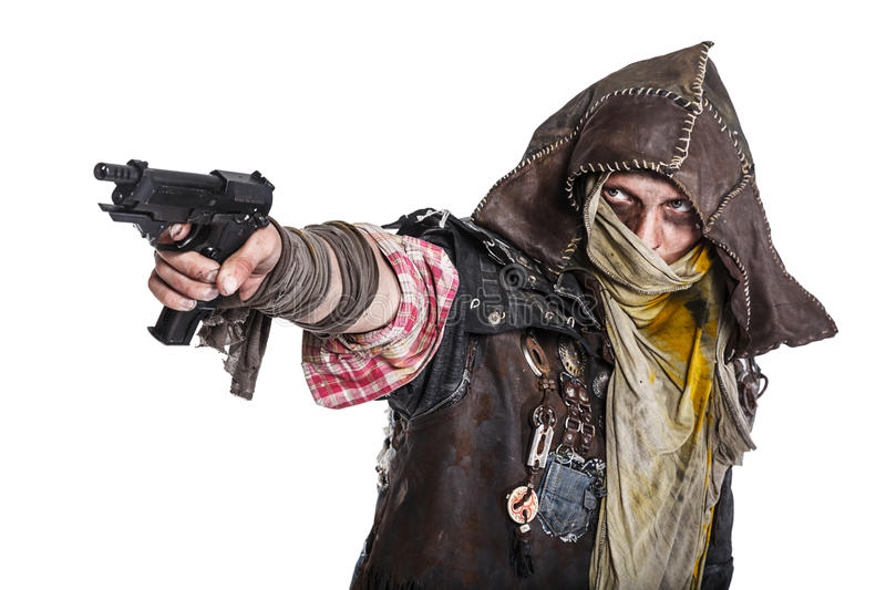 Post apocalypse survivor aiming a gun. Nuclear post apocalypse life after doomsday concept. Grimy survivor with homemade weapons aiming a gun. Studio closeup stock photography