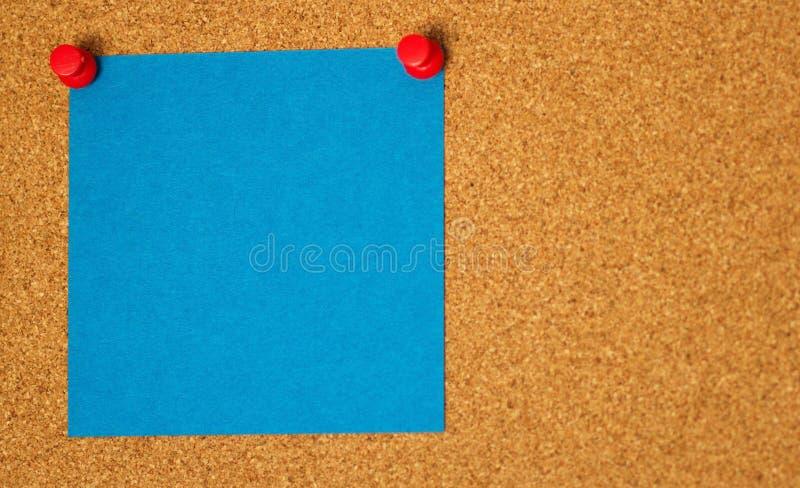 Post-it blu su un fondo di coarkboard fotografia stock libera da diritti