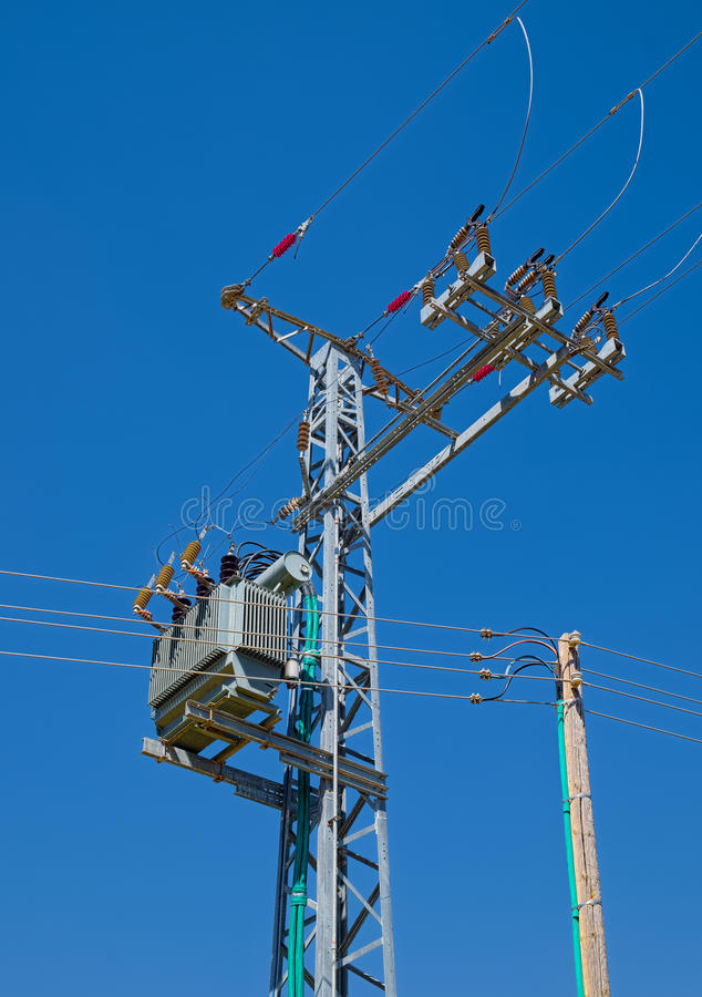 Post of electric power distribution. With high-voltage transformer mounted on a pylon, and power lines outgoing royalty free stock images