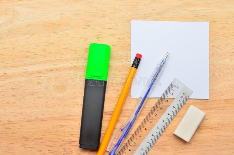 Post-it en blanco con la pluma, el lápiz, la regla, el mercado del punto culminante y el borrador en la tabla de madera de la ofi imagenes de archivo