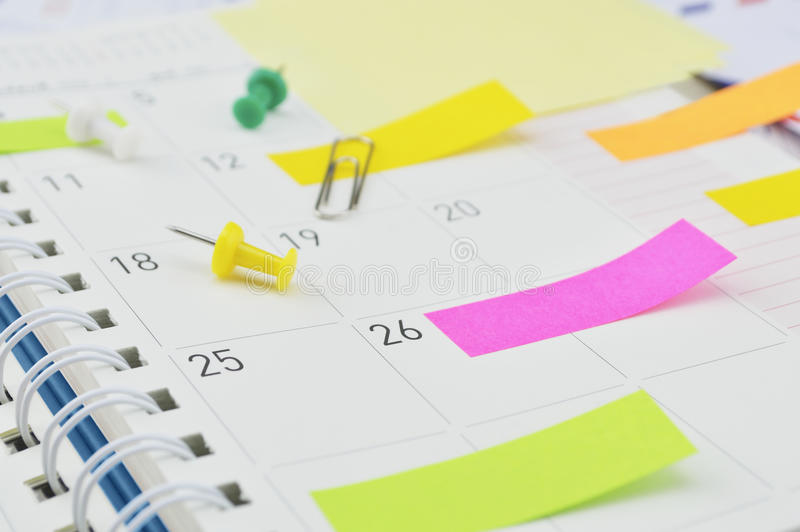 Post-Itanmerkungen mit Stift und Klipp auf Geschäftstagebuchseite stockfoto