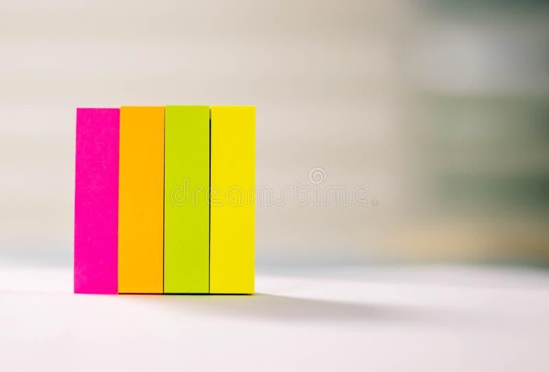 Post-it, klein, mehrfarbig, arrangiert auf dem Tisch platziert lizenzfreie stockfotos