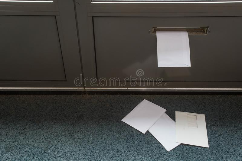 Post lying on the floor and in the door mailbox in a empty building. Close-up delivery letter letterbox envelope front house postman news package paper postage royalty free stock photo