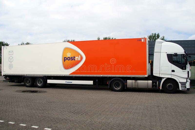 Post NL delivery truck - side view. Almere, Flevoland, The Netherlands - May 16, 2015: PostNL truck parked in front of a office building. PostNL is a mail stock photo