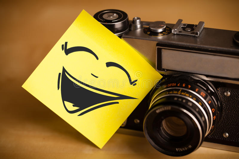 Post-it Note With Smiley Face Sticked On Photo Camera Royalty Free Stock Images